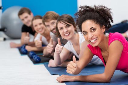 gruppe im sportstudio zeigt daumen hoch